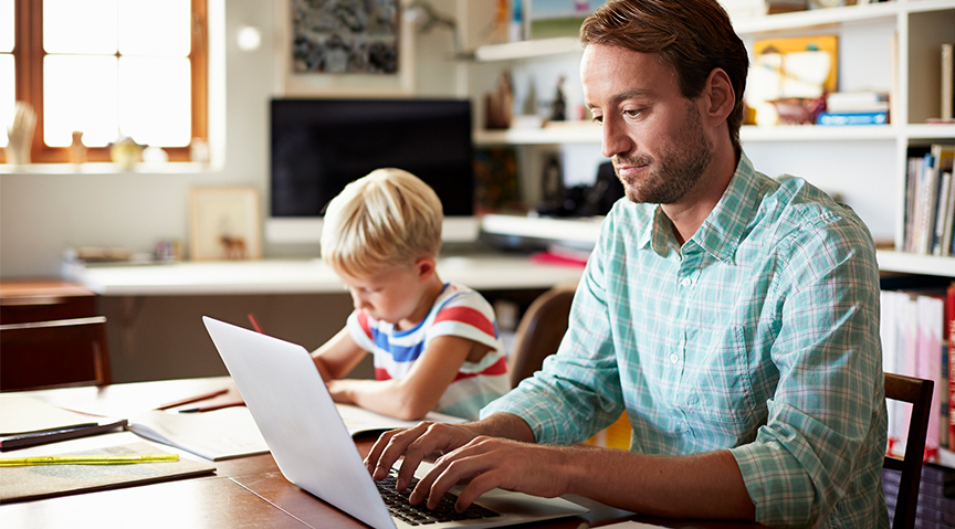 Father on laptop next to son