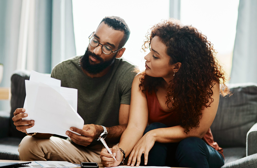 mixed couple on couch reviewing papers