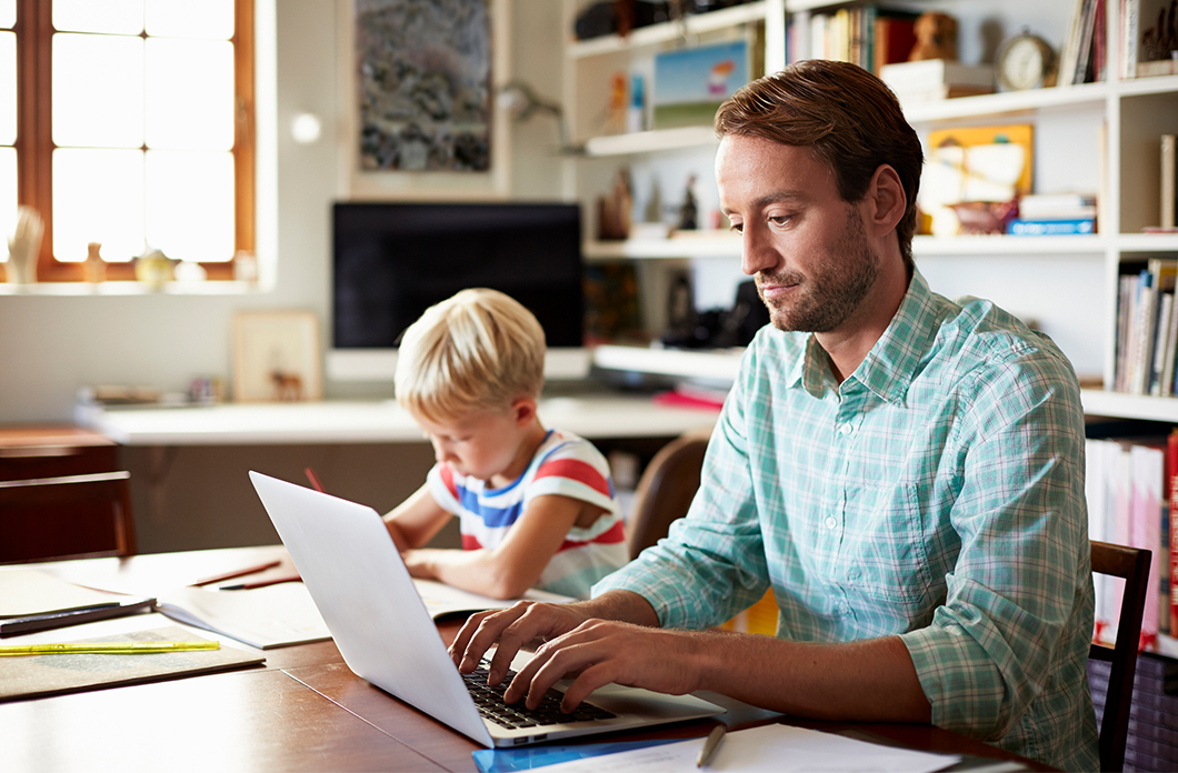 father on laptop next to son at table